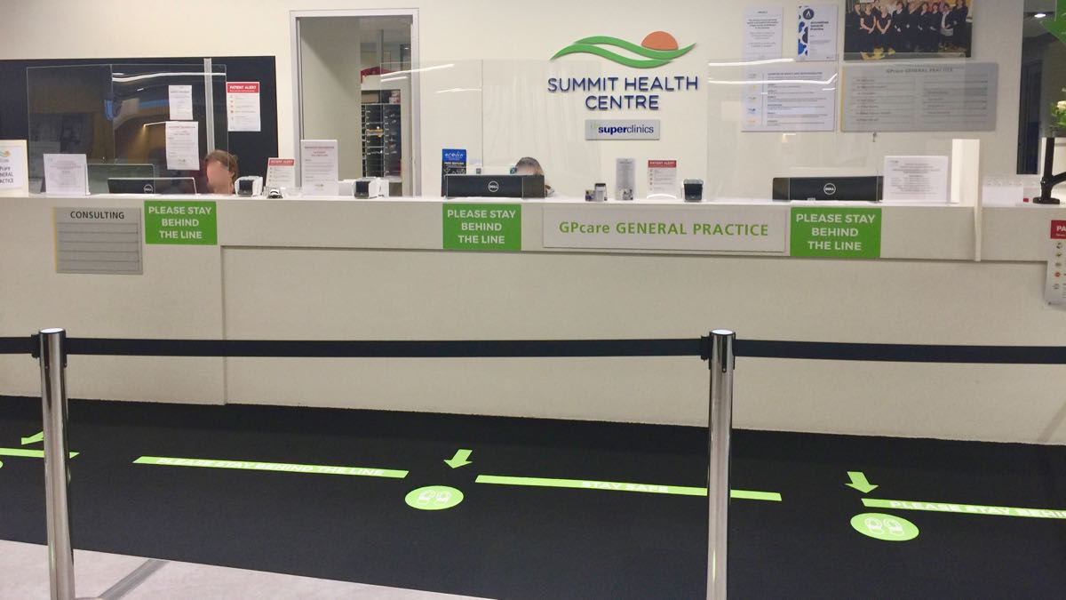 social distancing stickers were installed on reception counter and carpet at the Summit Health Centre by WallsThatTalk